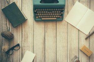 ripiano con macchina da scrivere, occhiali, fogli e libri